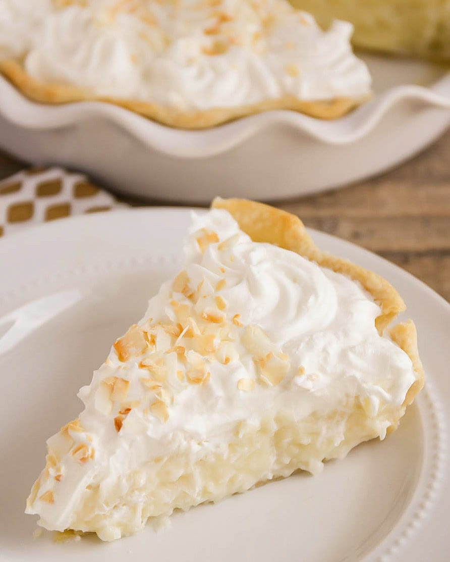 A slice of coconut pie on a white plate