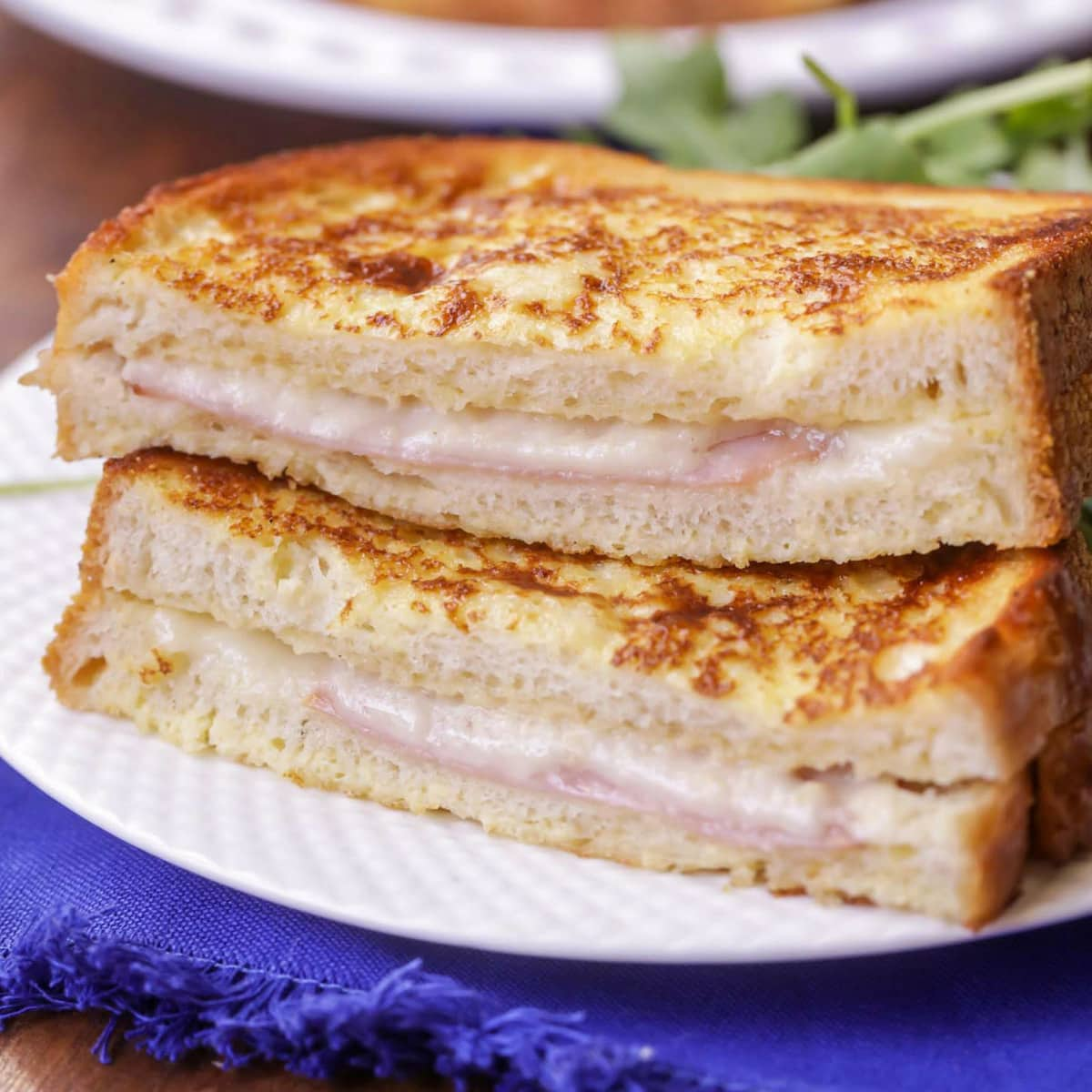 Croque Monsieur cut in half and placed on a white plate