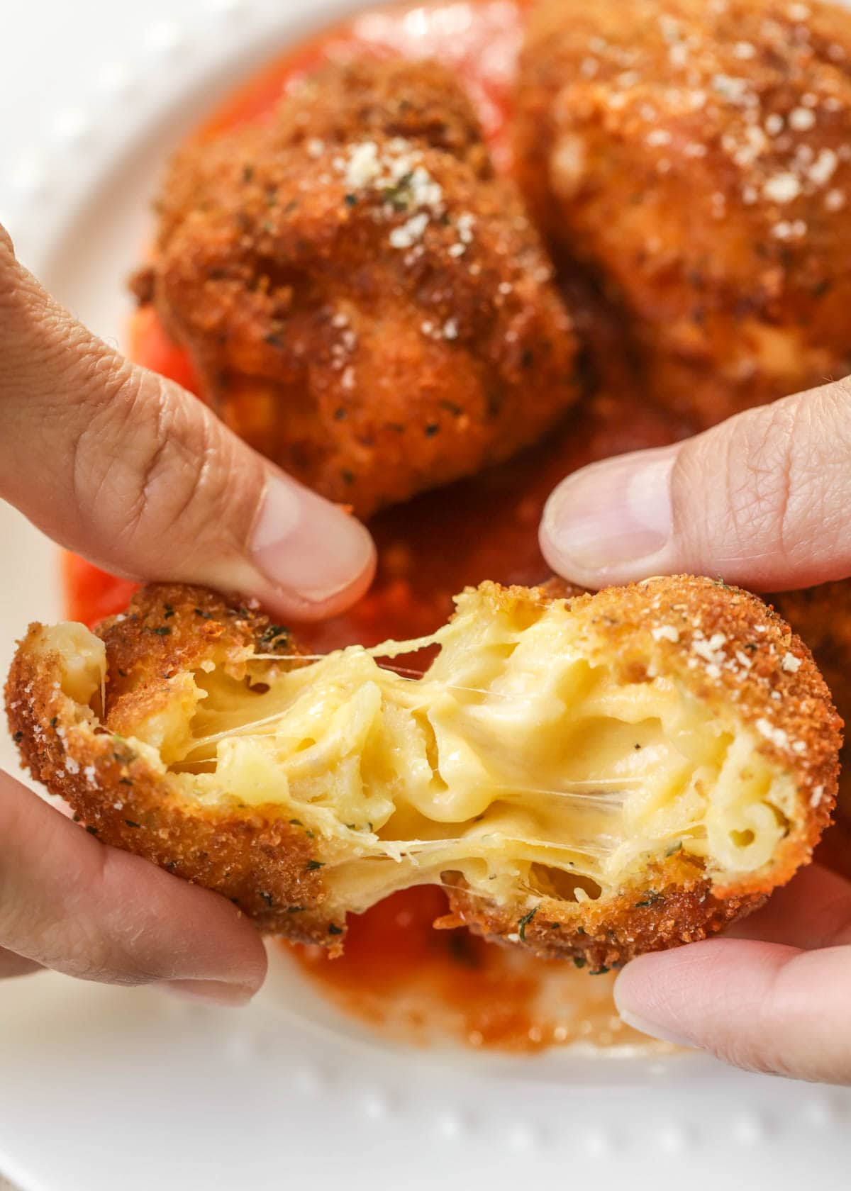 Two hands pulling apart a fried mac and cheese ball revealing the gooey center