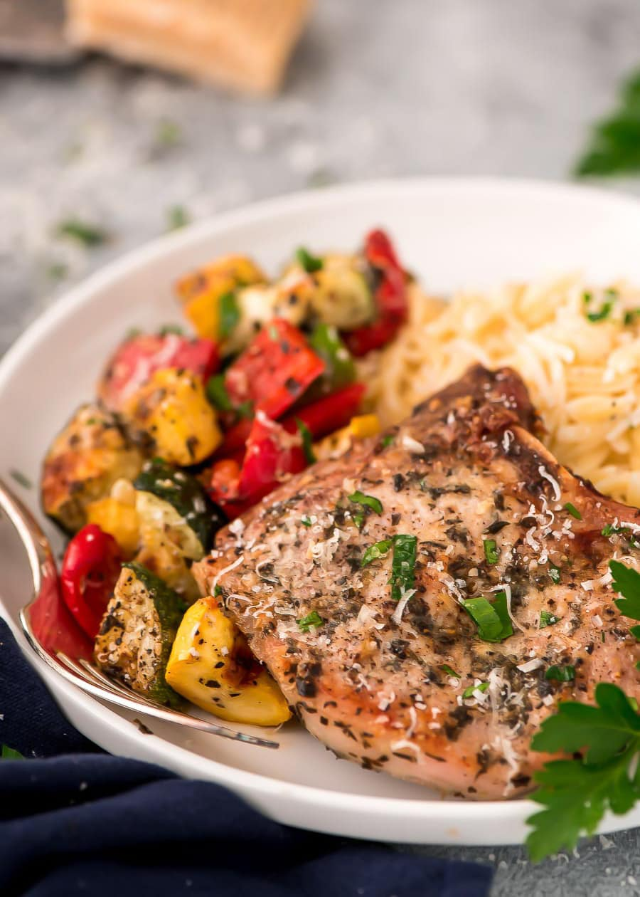 Closeup of a baked Italian pork chop on a plate with vegetables and pasta