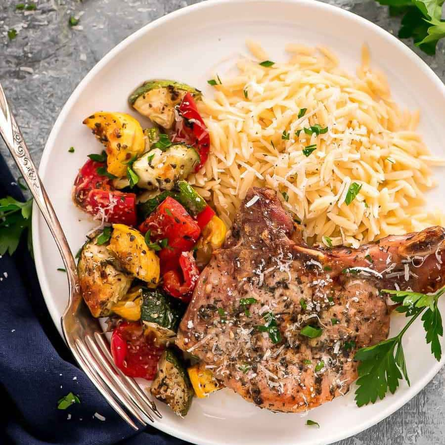 An Italian seasoned pork chop on a plate with orzo pasta and veggies