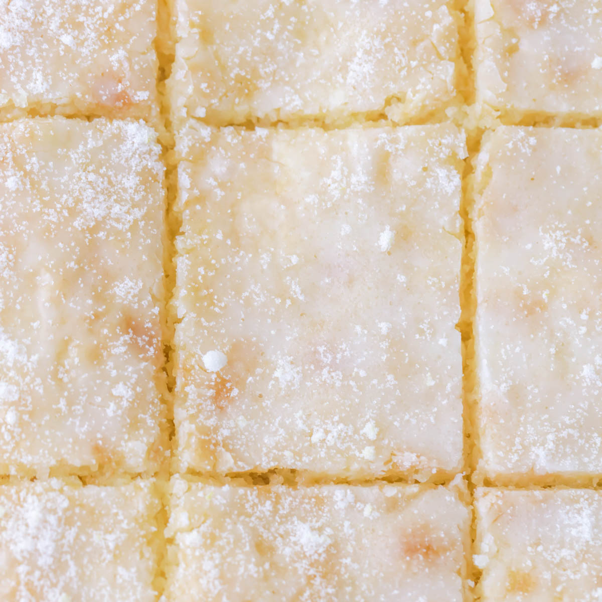 Lemon cake squares cut in a pan.