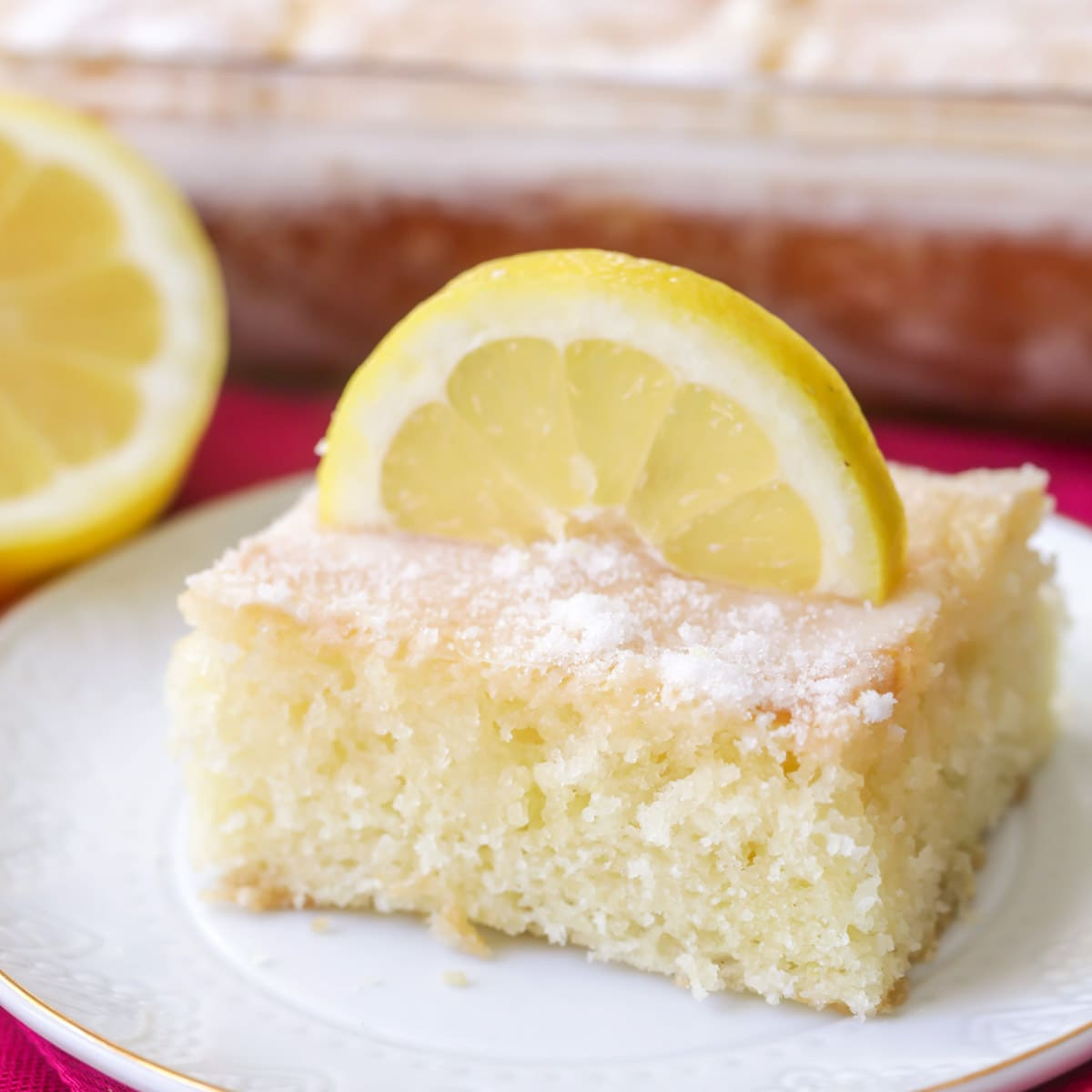 Lemon buttermilk cake garnished with a slice of lemon on a white plate.