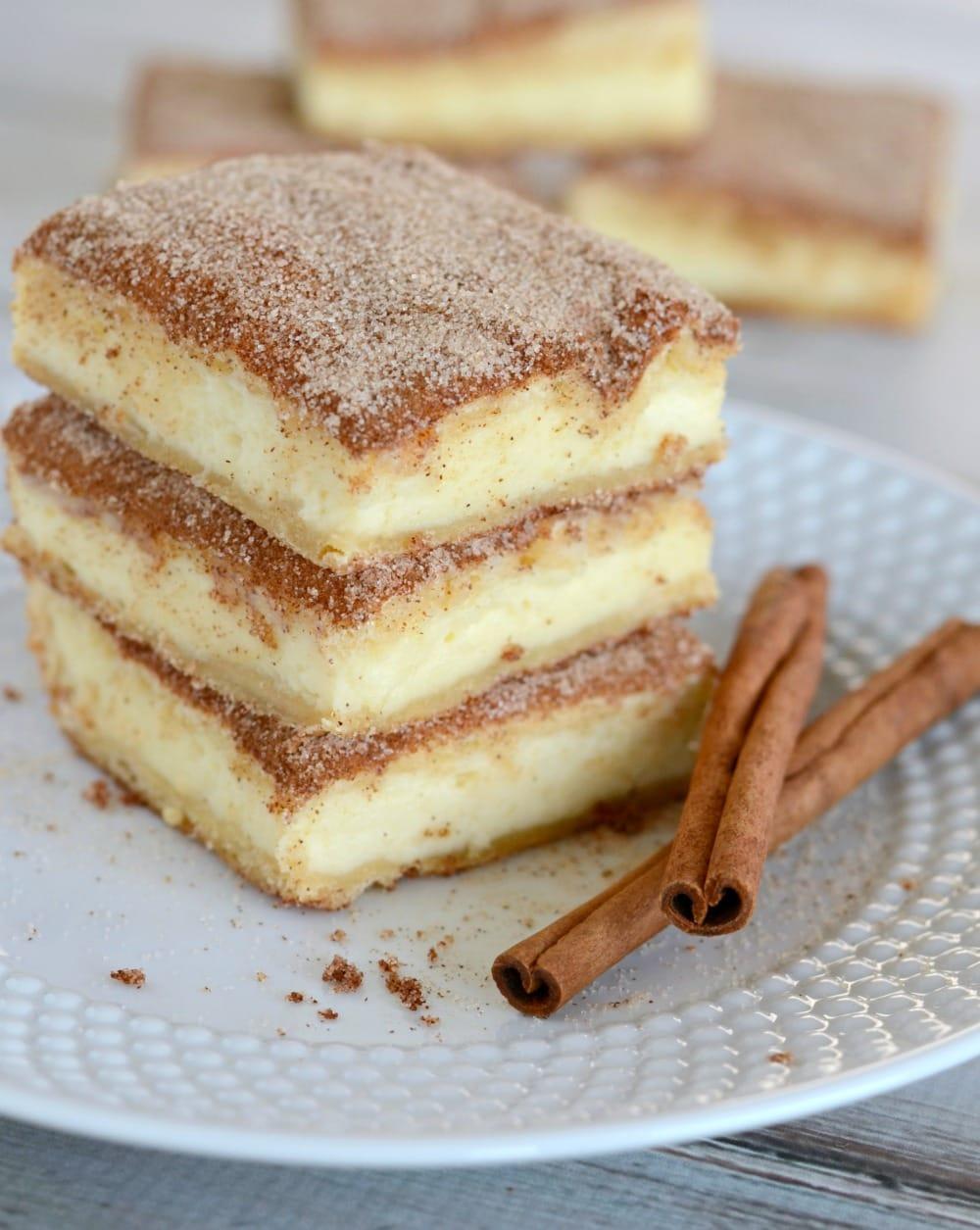 Churro Cheesecake bars stacked on a white plate