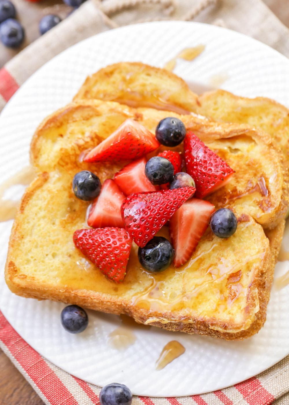 Eggnog french toast topped with berries on a white plate