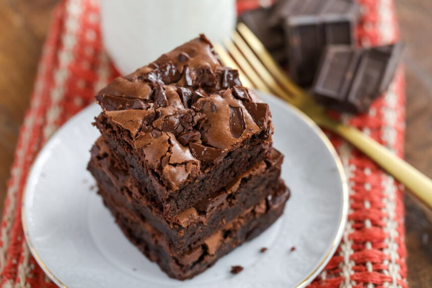 Three fudgy brownies stacked on a white plate