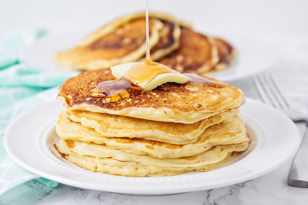 Oatmeal pancake recipe - stacked with butter and syrup on white plate