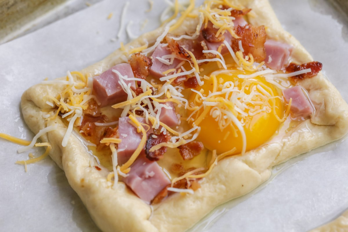 Close up of uncooked breakfast hand pie topped with ham, egg cubes, and cheese.