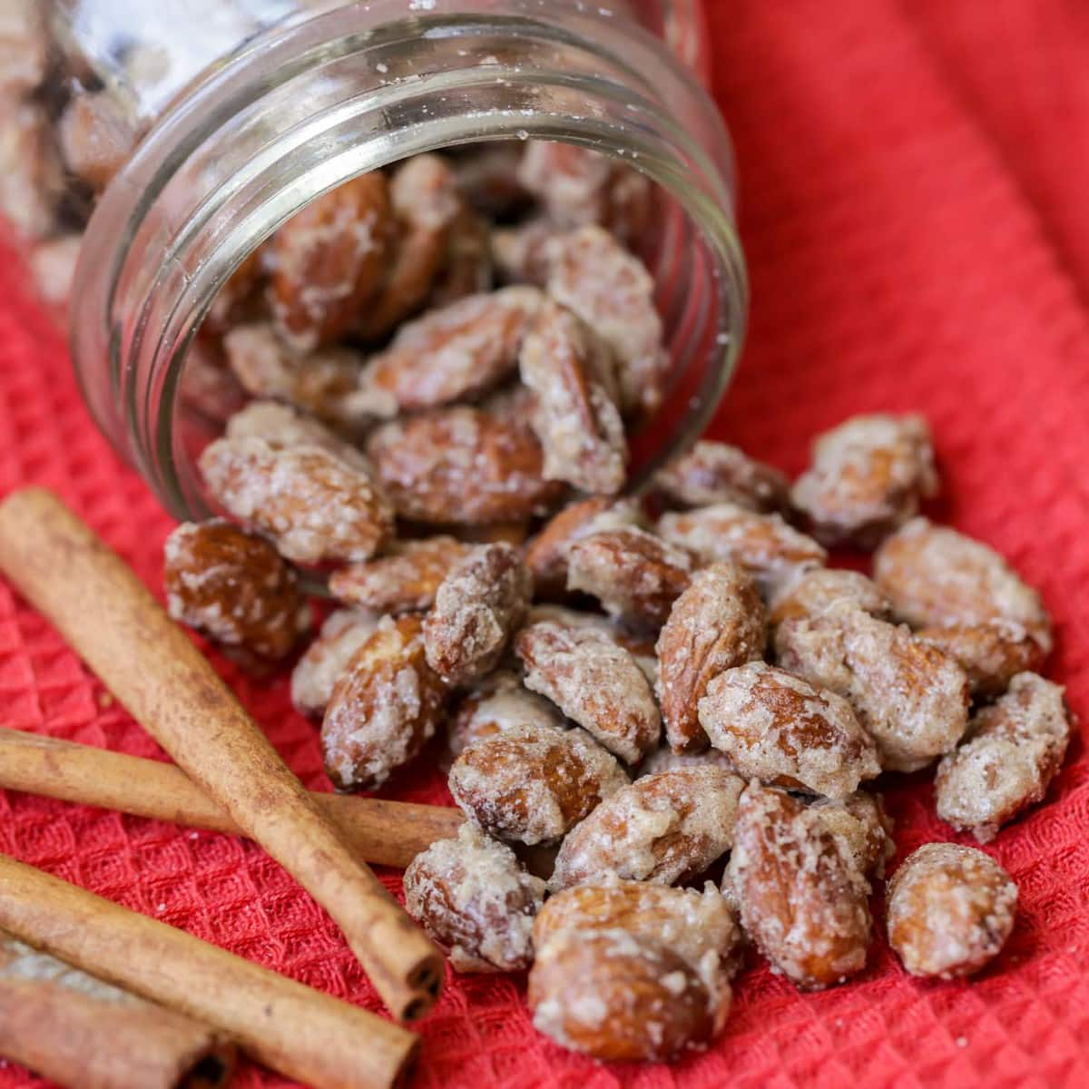 Candied almonds spilling out of a mason jar