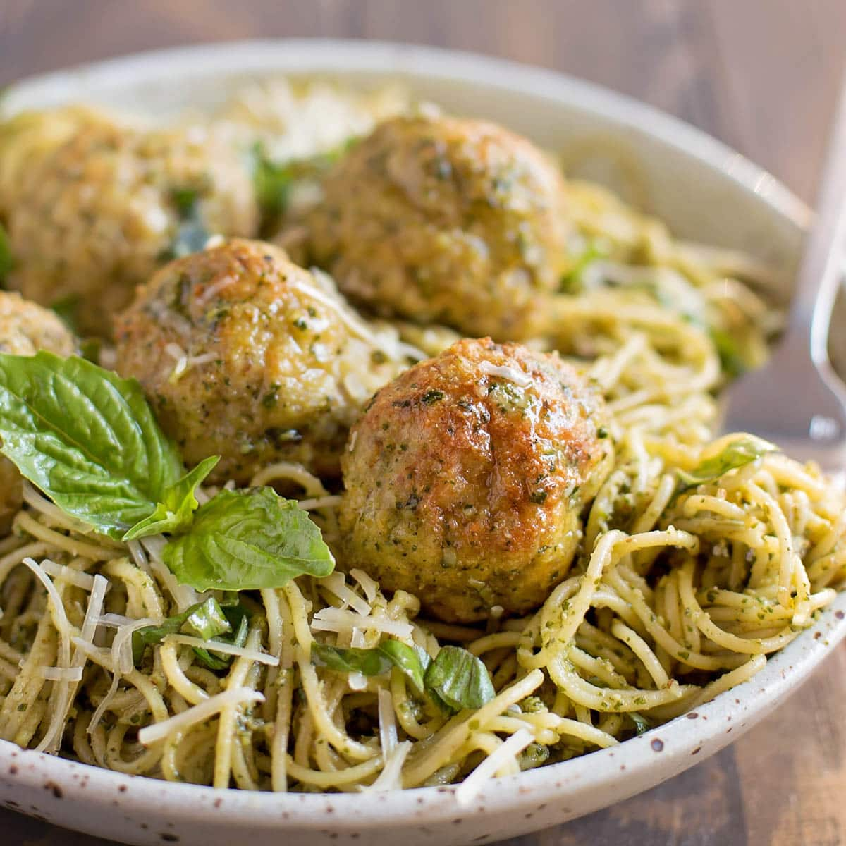Chicken pesto meatballs served with a bowl of pesto pasta
