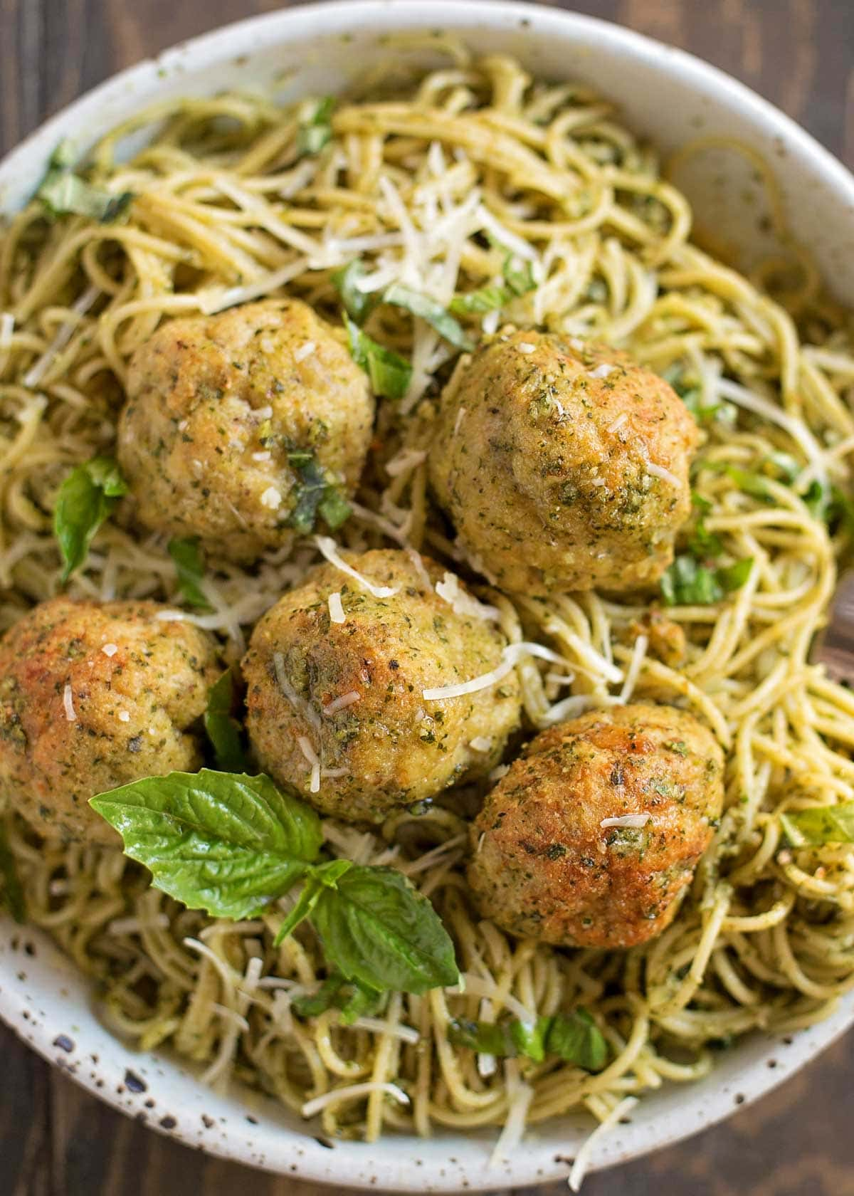 Pesto chicken meatballs on top of pesto pasta in a bowl