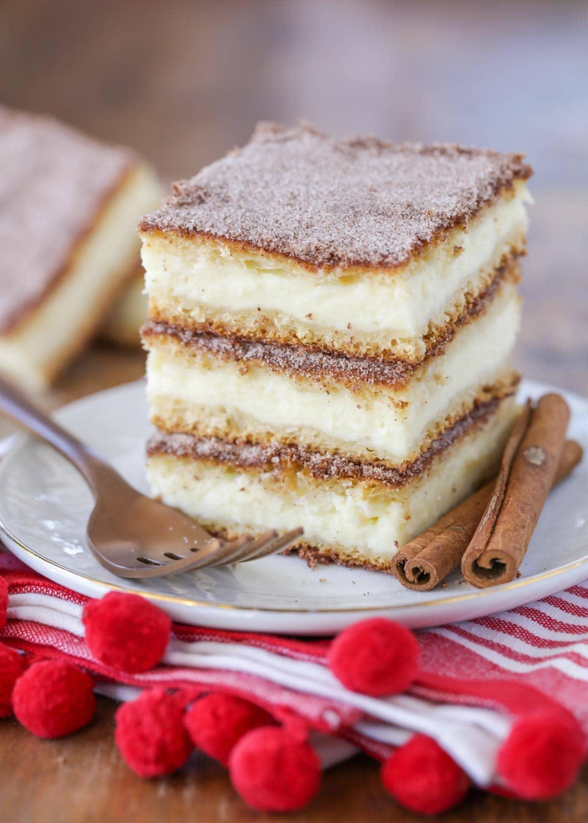 Stack of cut churro cheesecake bars on a white plate.