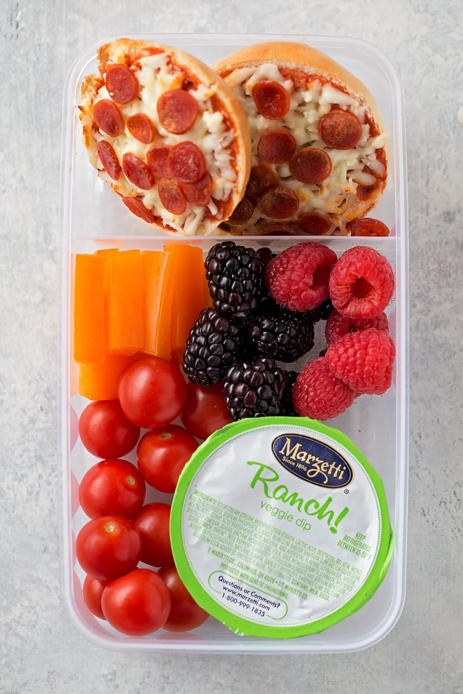 easy lunch box idea with mini pizza bagels, berries, carrots, and tomatoes