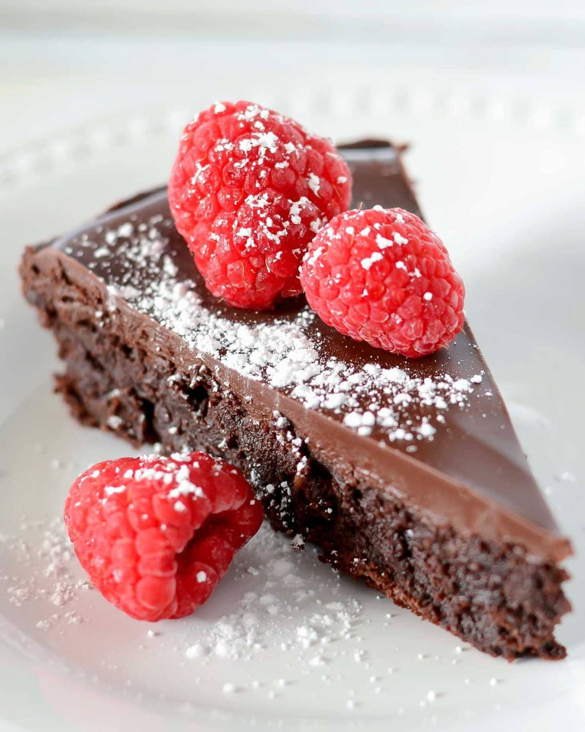 Best Flourless Chocolate Cake topped with raspberries and powdered sugar