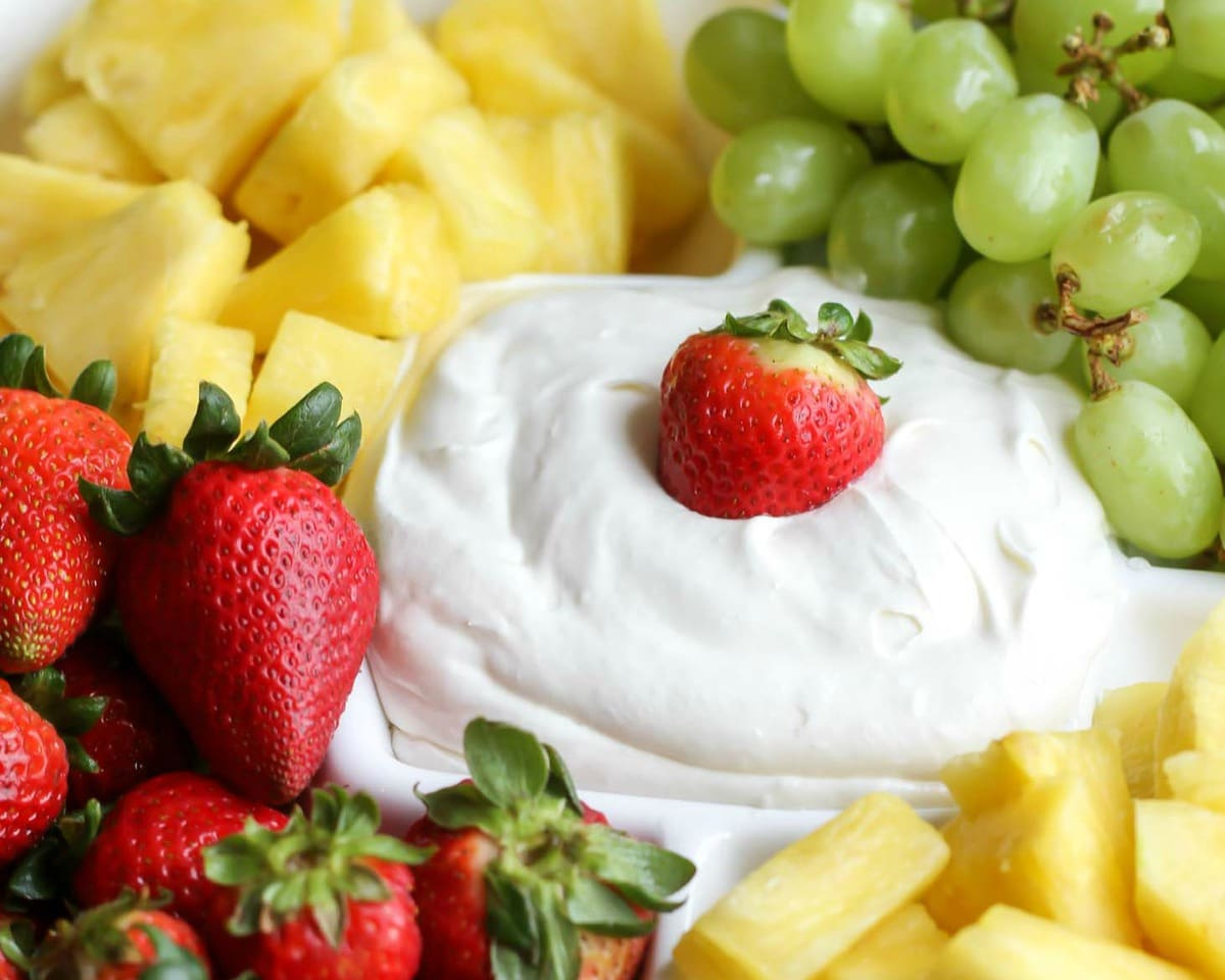 cream cheese fruit dip with a strawberry on top surrounded by other fruits