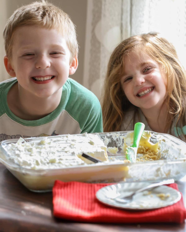 Two children smiling next to pan full of white chocolate lasagna
