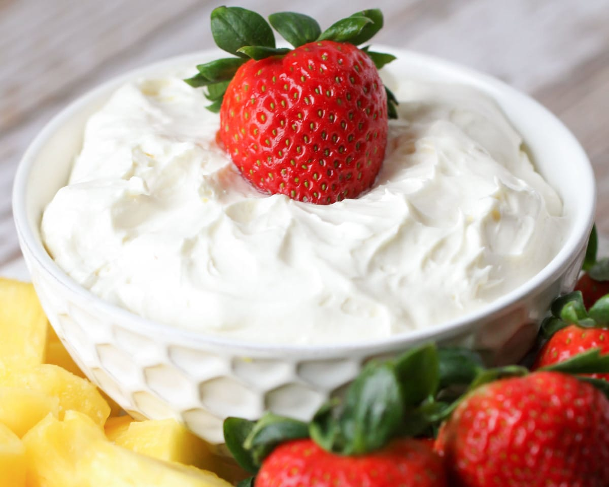 Vanilla yogurt fruit dip with strawberries and pineapple on the side