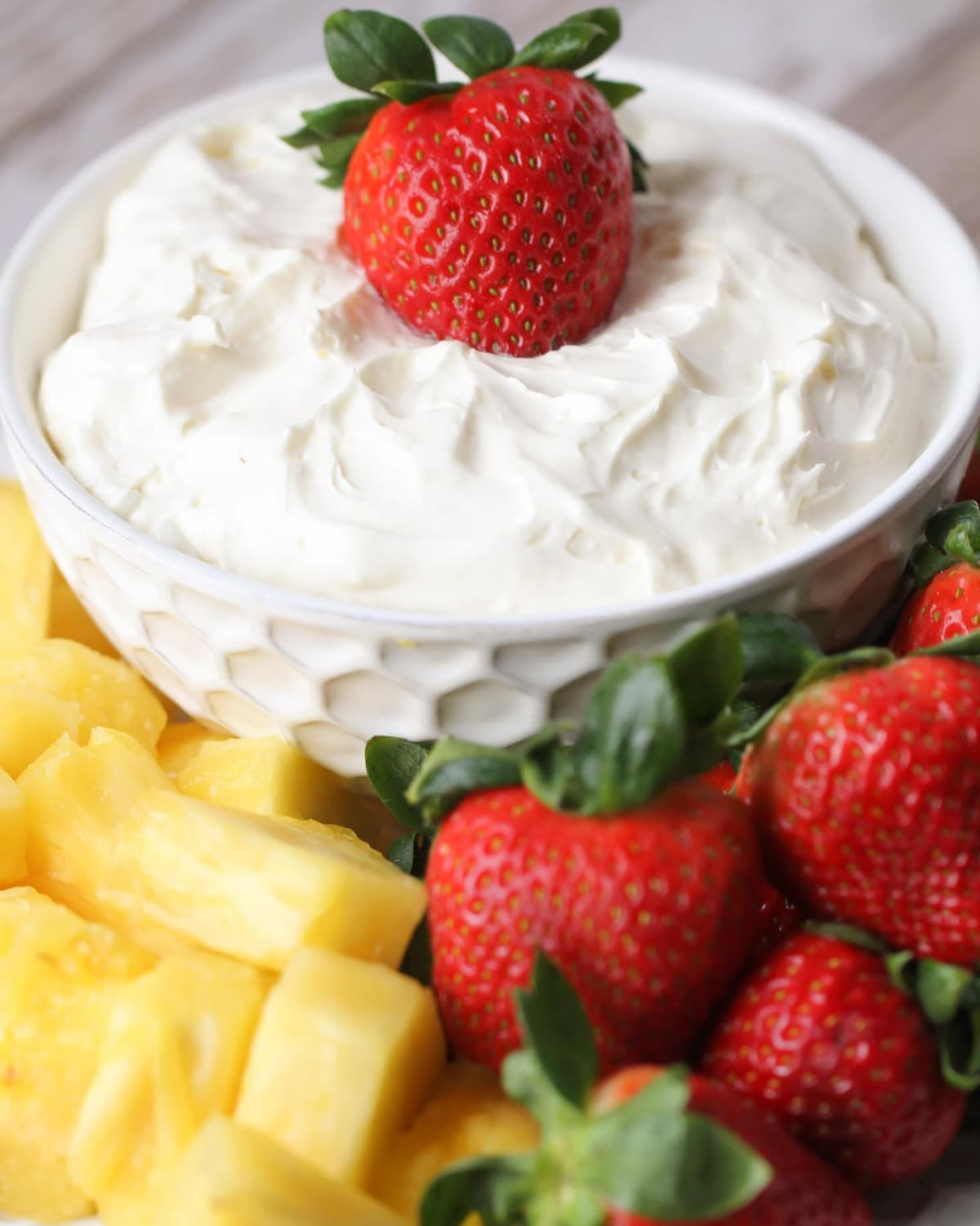Vanilla yogurt fruit dip in a serving bowl with fruit on the side