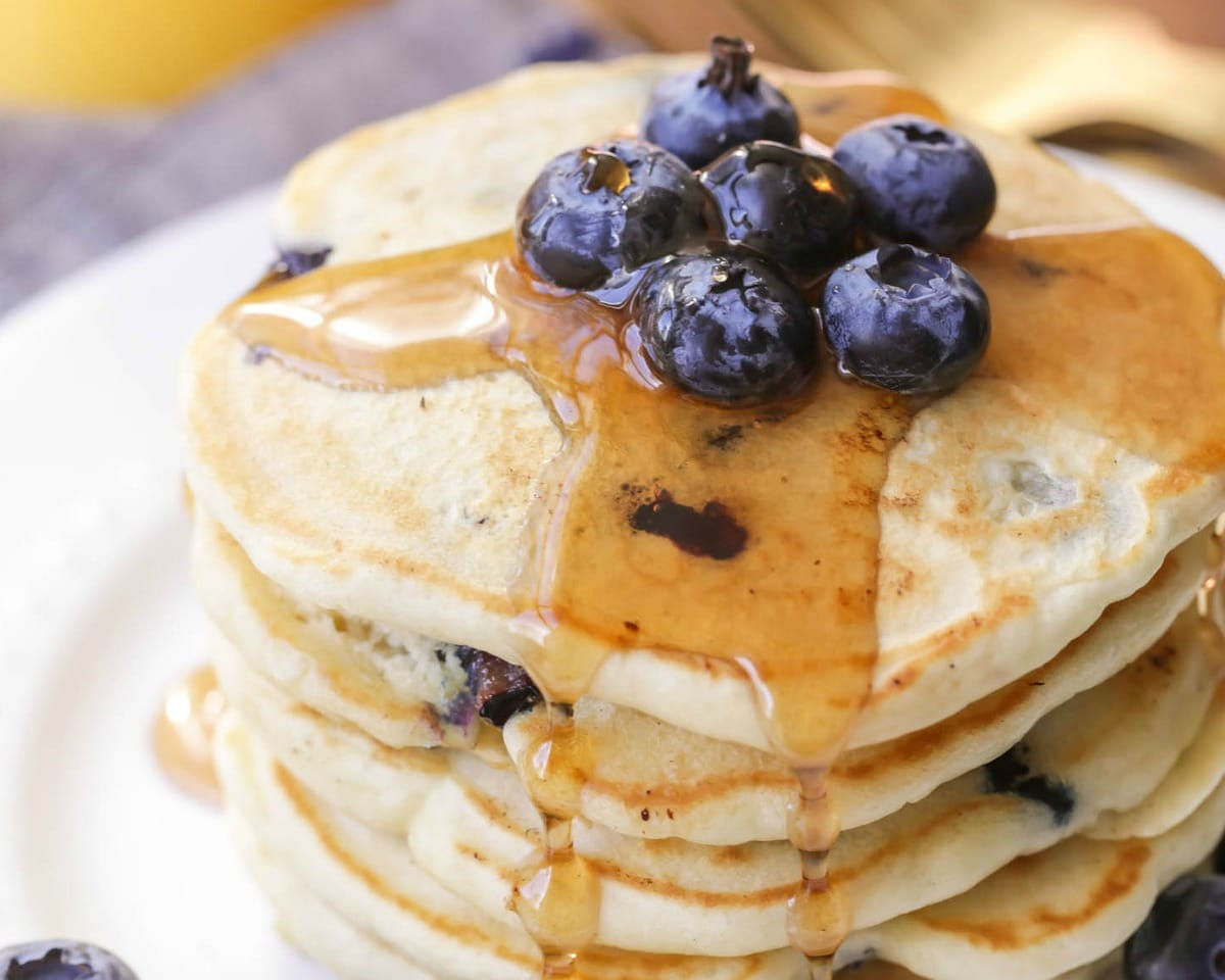 Blueberry Pancakes stacked on a white plate and topped with blueberries