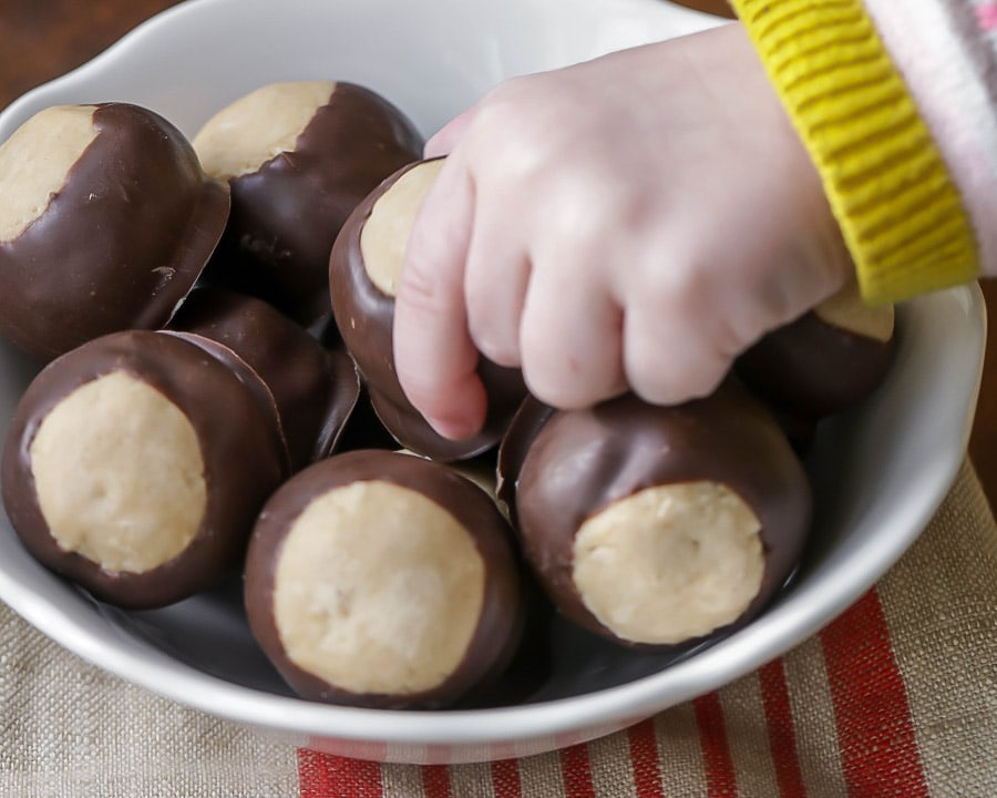 A child's hand taking a buckeye ball out of the bowl