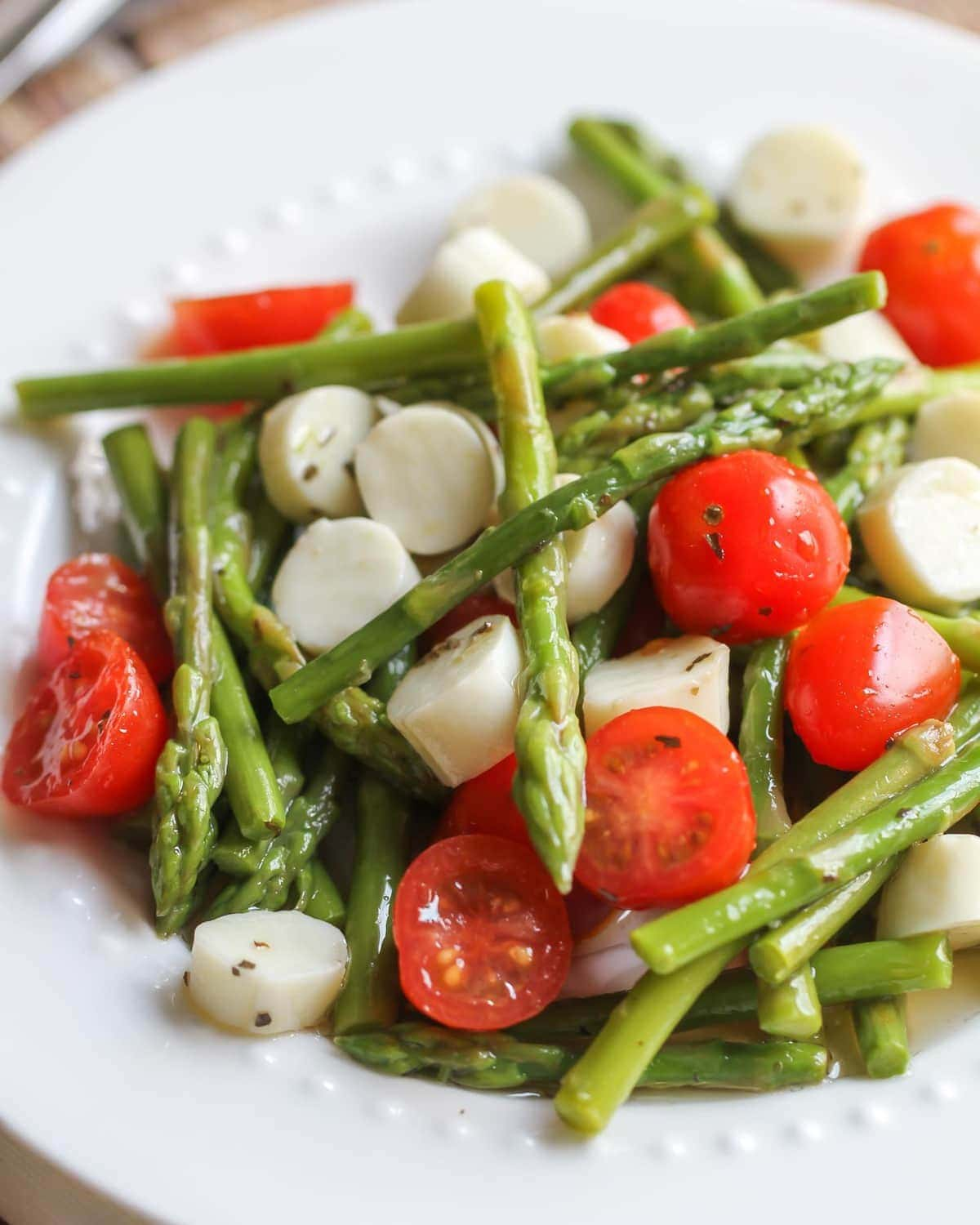 Cold asparagus salad in a white dish