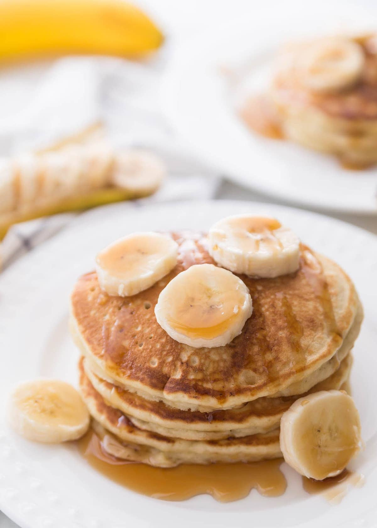 Banana Pancakes stacked on plate with fresh bananas on top
