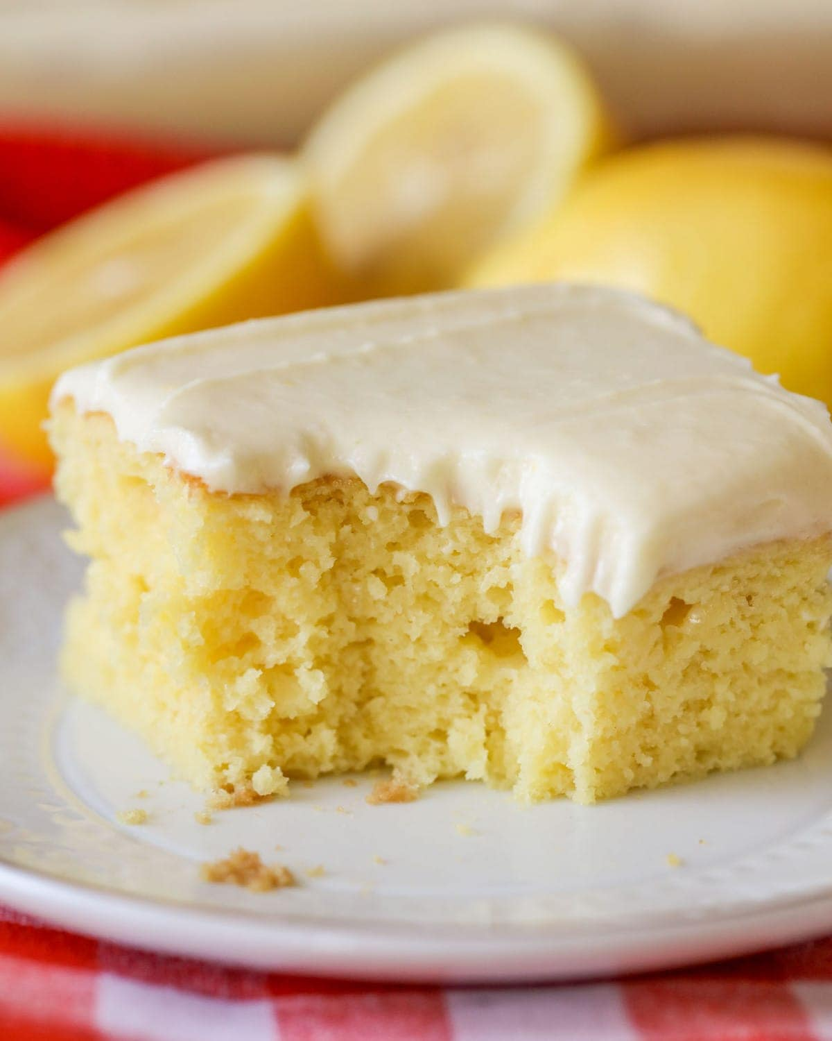 homemade lemon cake with lemon frosting on a white plate