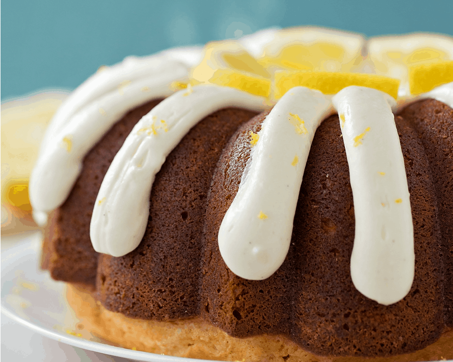 Lemon Bundt Cake topped with cream cheese frosting and lemon wedges