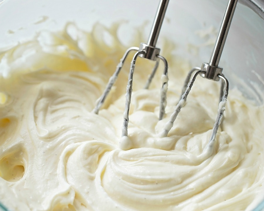 bundt cake icing being mixed with a hand mixer