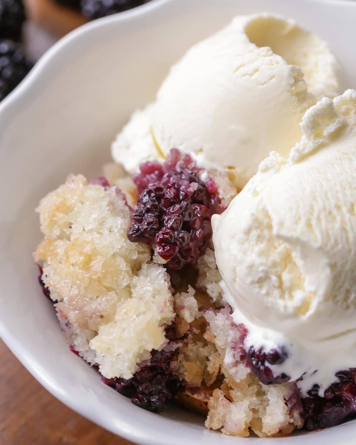 Blackberry cobbler in a bowl with two scoops of vanilla icecream