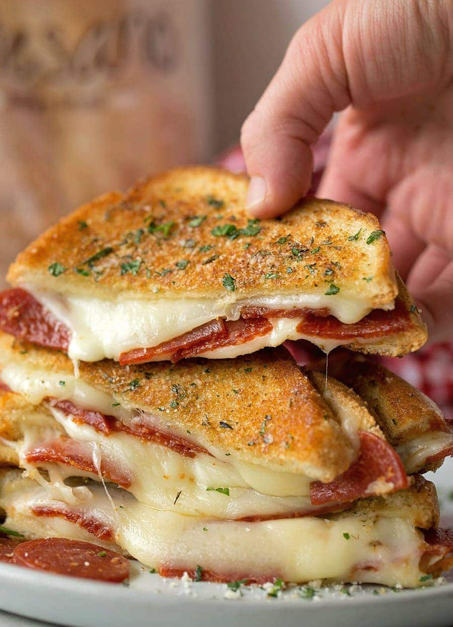 Pizza grilled cheese sandwiches stacked on a plate