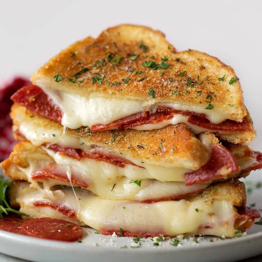 Pizza grilled cheese sandwiches cut in half and stacked on a plate