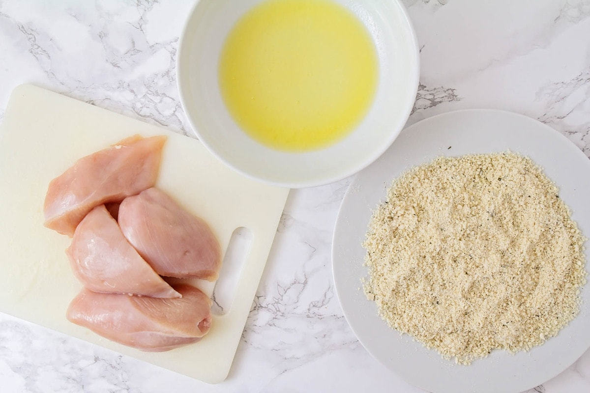Chicken breasts next to bowl of melted butter and bowl of breading for chicken
