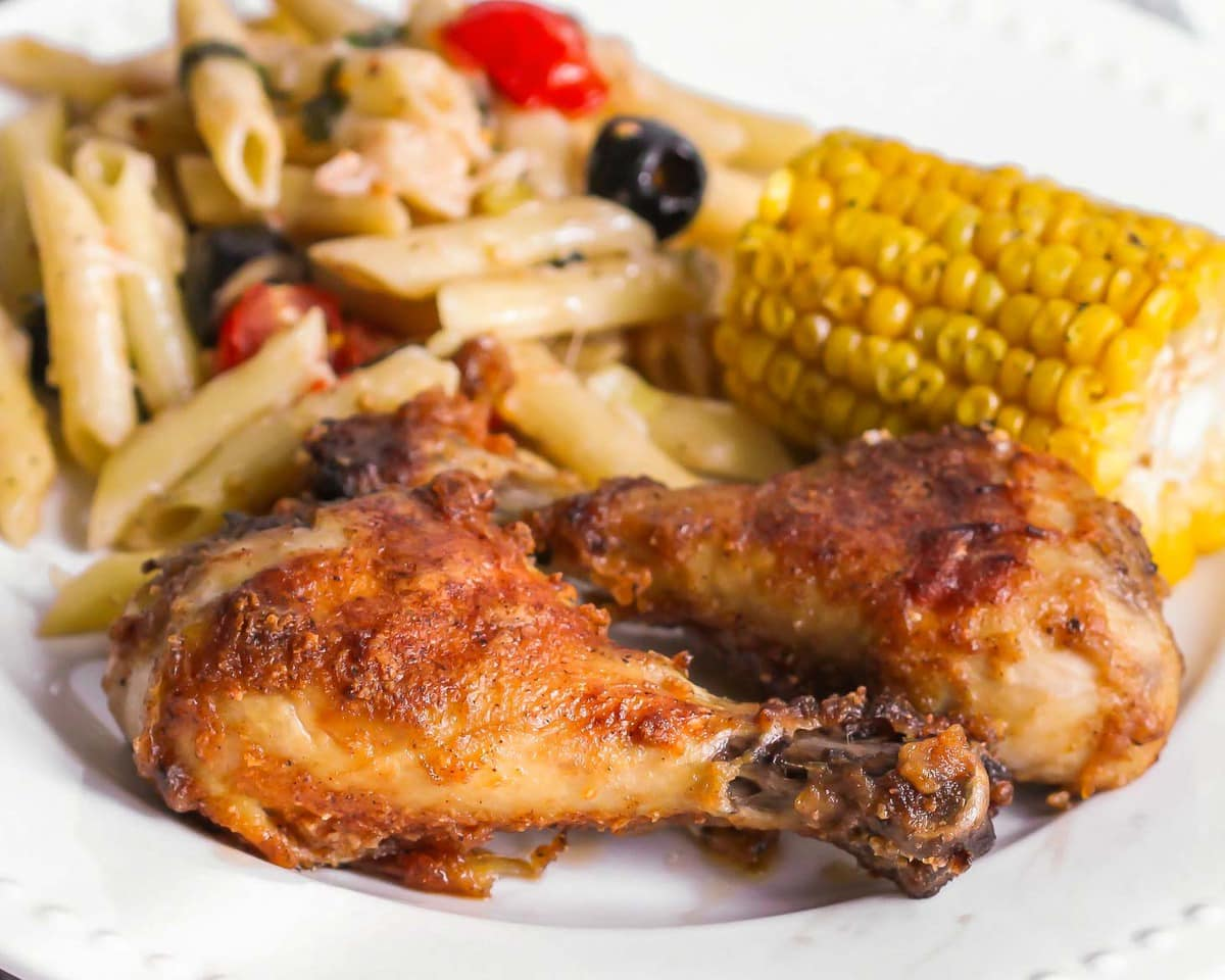 Two Chicken Drumsticks on a plate with a side of pasta salad and corn