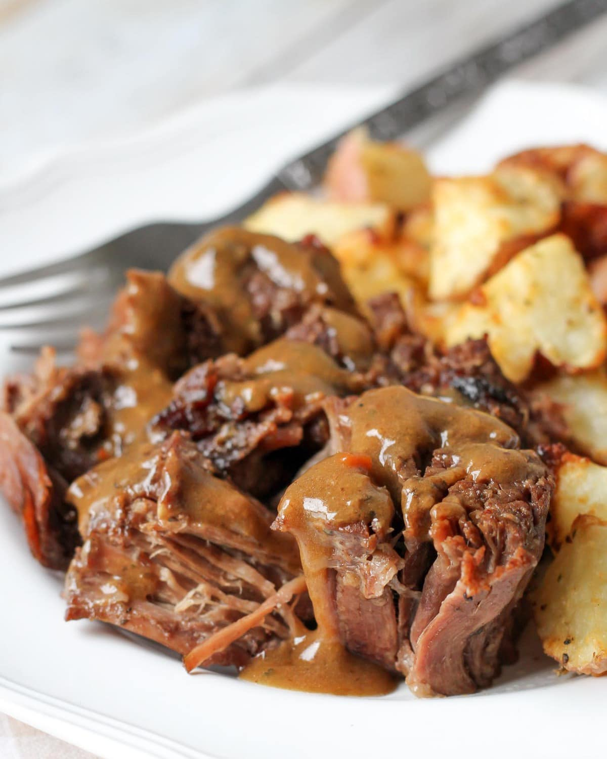 Chuck Roast Crock Pot Recipe on plate with gravy