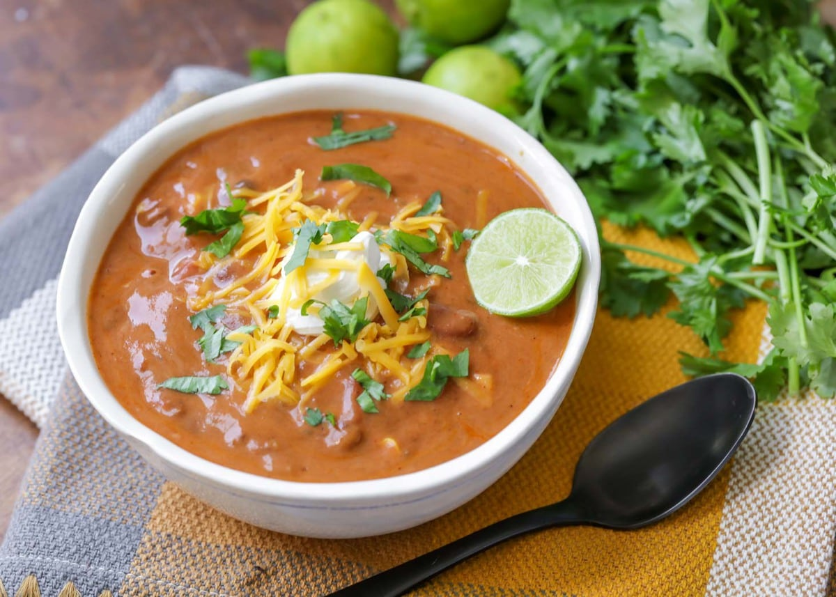 Slow cooker taco soup topped with sour cream, shredded cheese, and cilantro