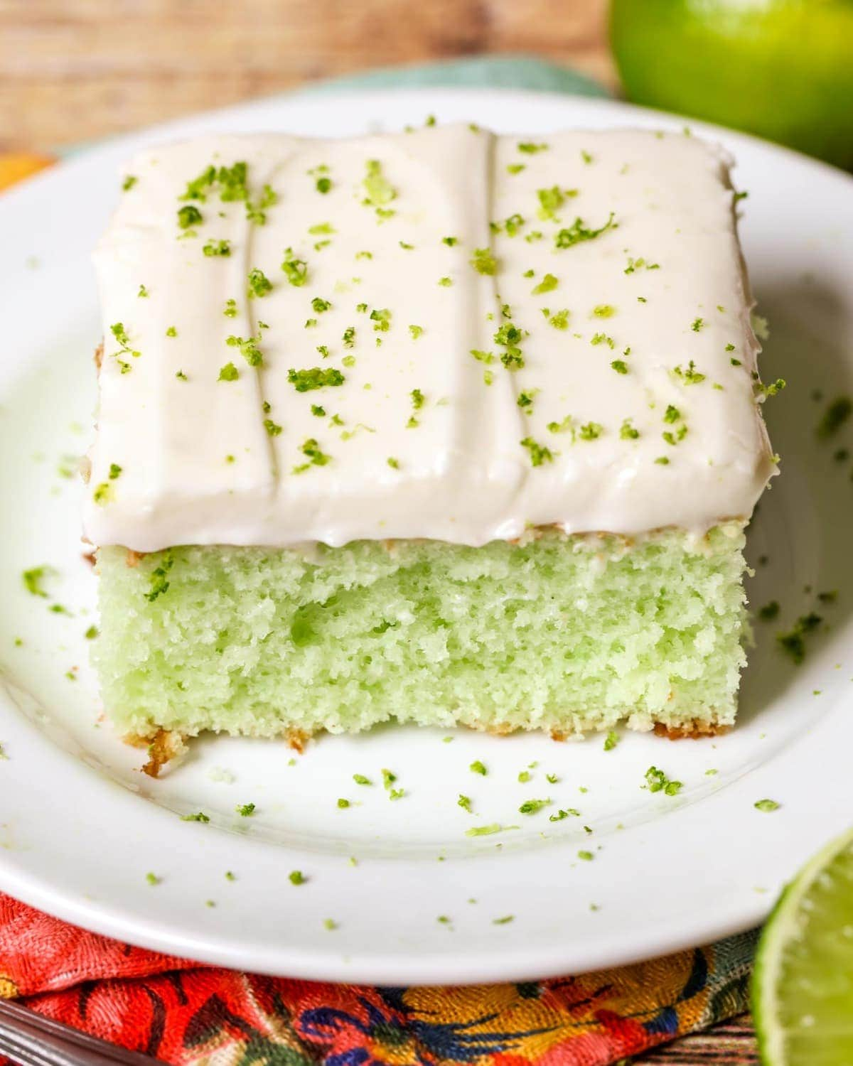 lime jello cake topped with frosting and lime zest