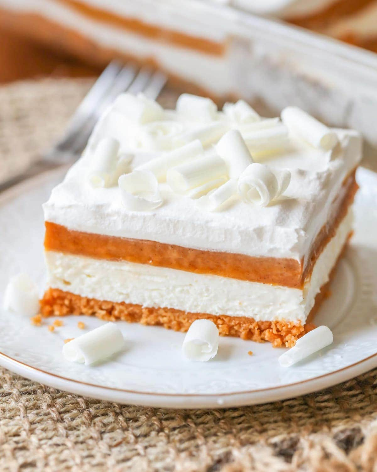 Pumpkin Lasagna Dessert topped with white chocolate curls on a white plate