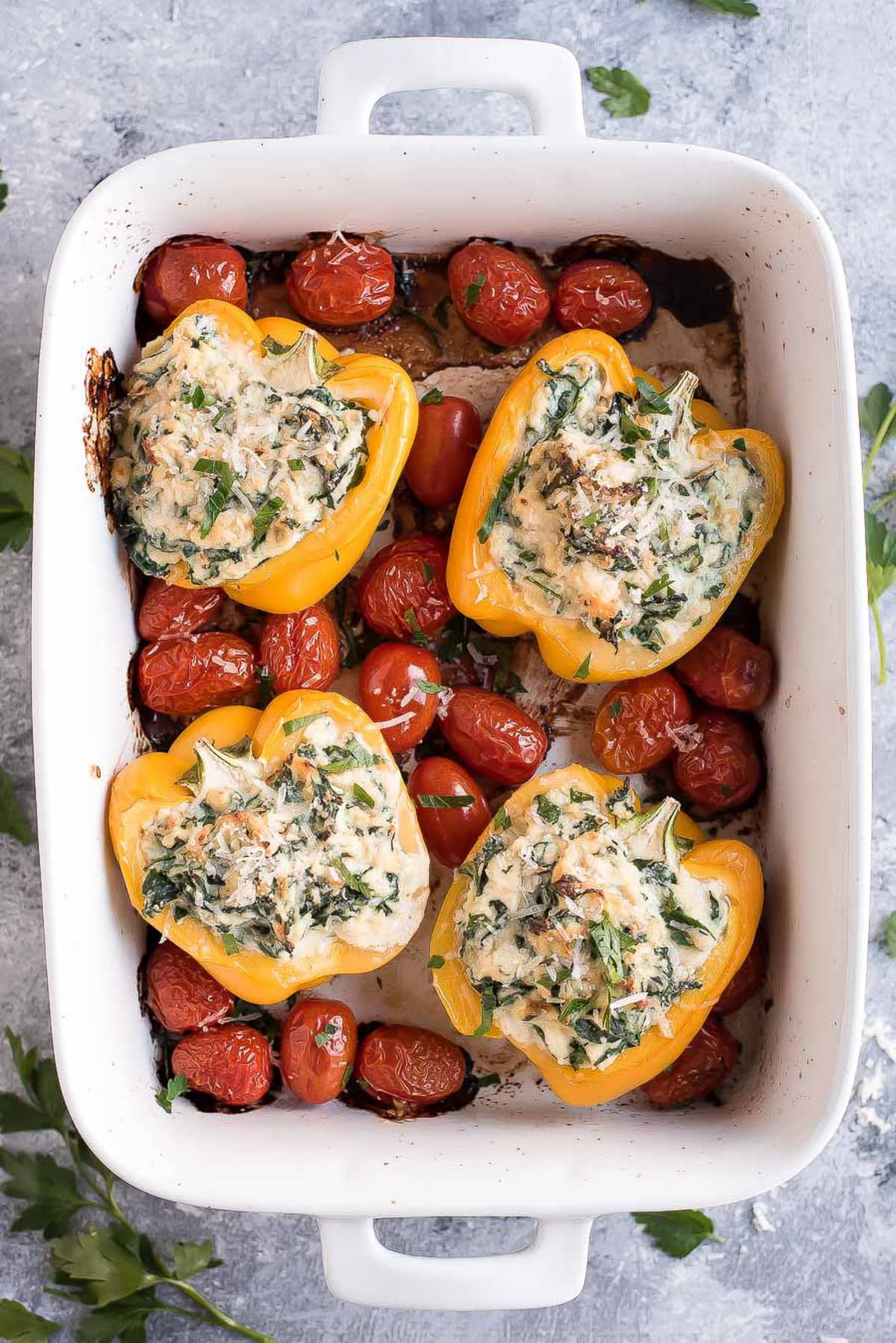 Easy Stuffed Bell Peppers and grape tomatoes in a white baking dish