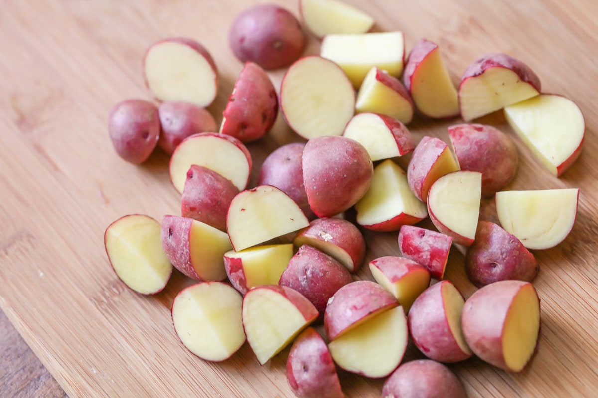 Cut up red potatoes on cutting board