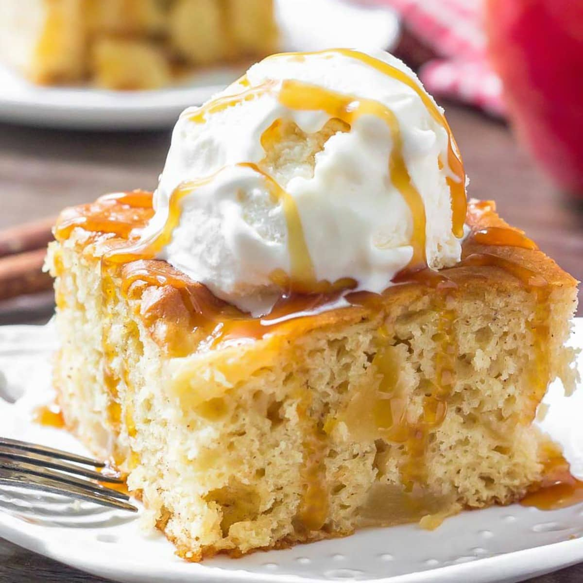 a slice of Apple Cake topped with ice cream and caramel sauce