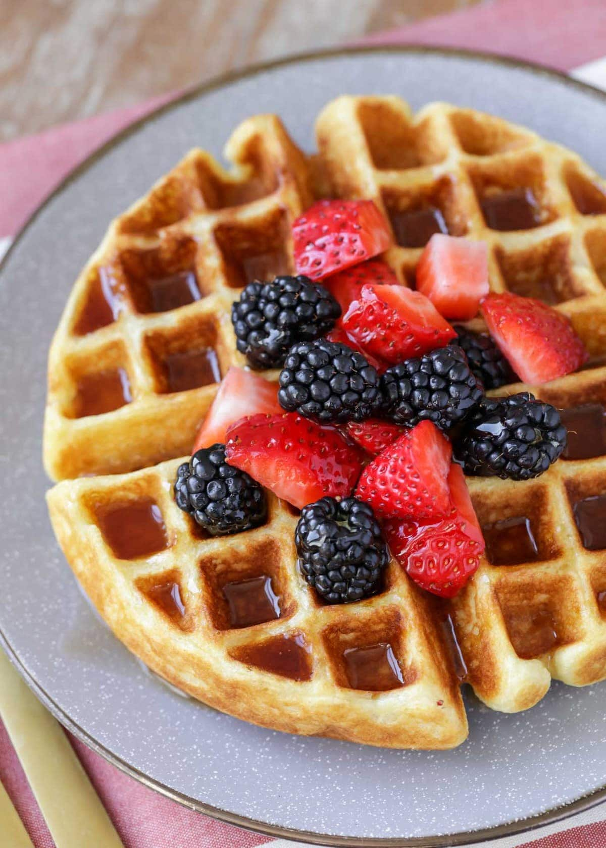 Belgian waffles recipe topped with berries on gray plate