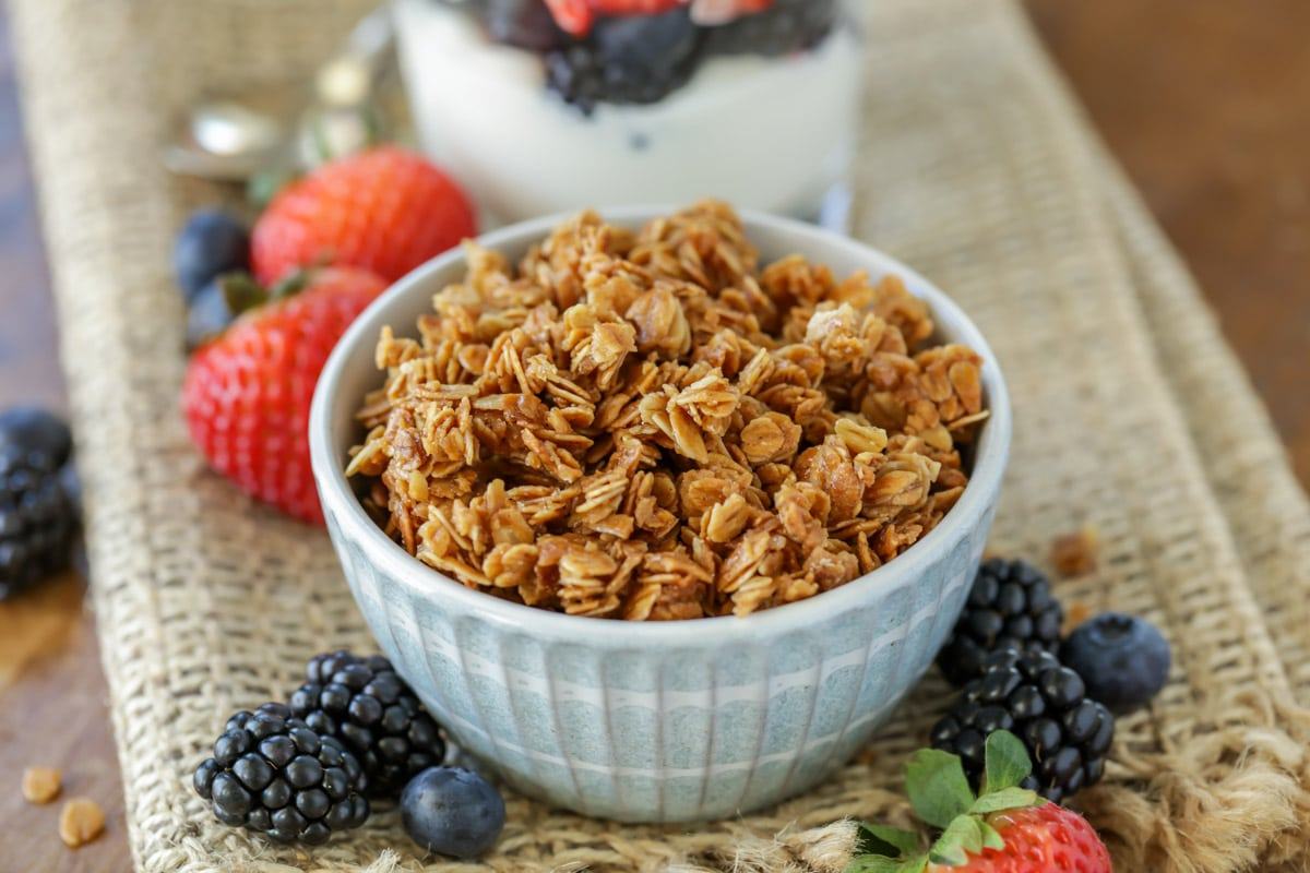 homemade granola in a blue bowl surrounded by berries