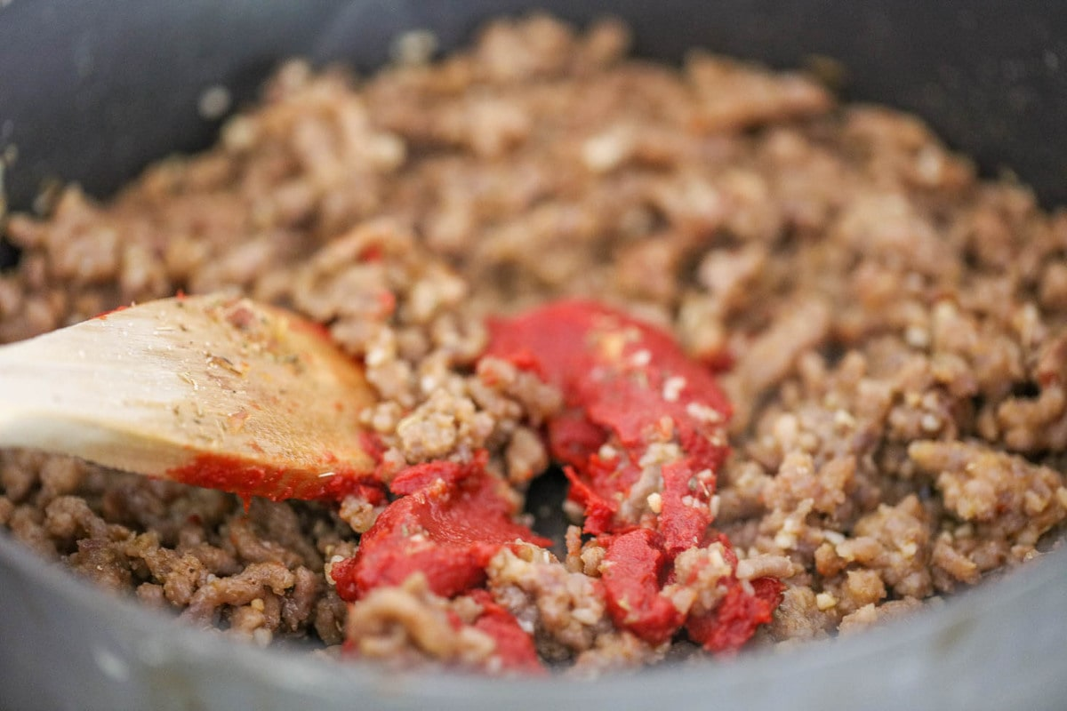 Cooking meat and tomato paste in a pot for lasagna soup