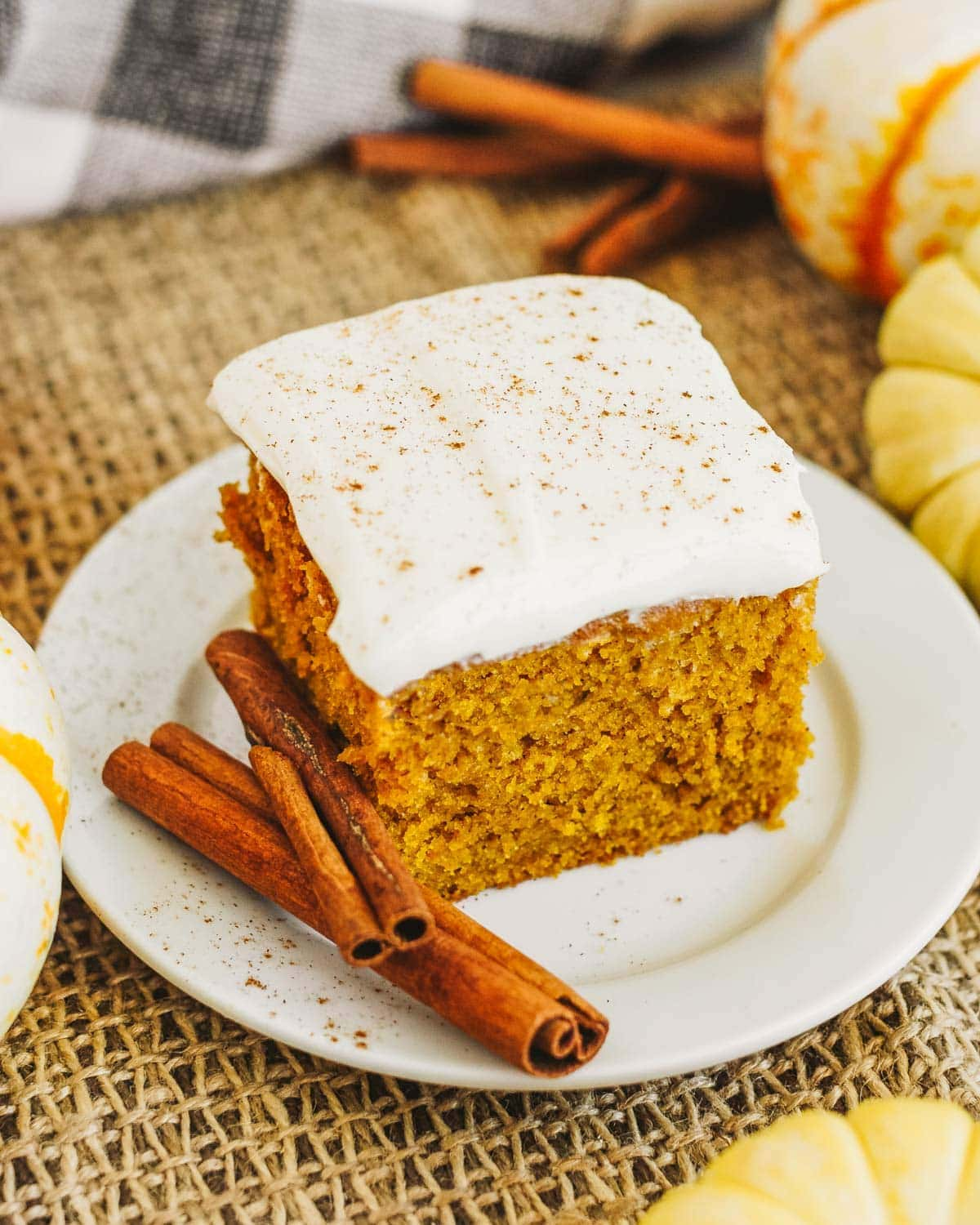 Pumpkin cake recipe slice on plate with cinnamon sticks