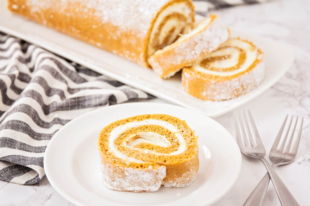 A slice of pumpkin roll on a white plate