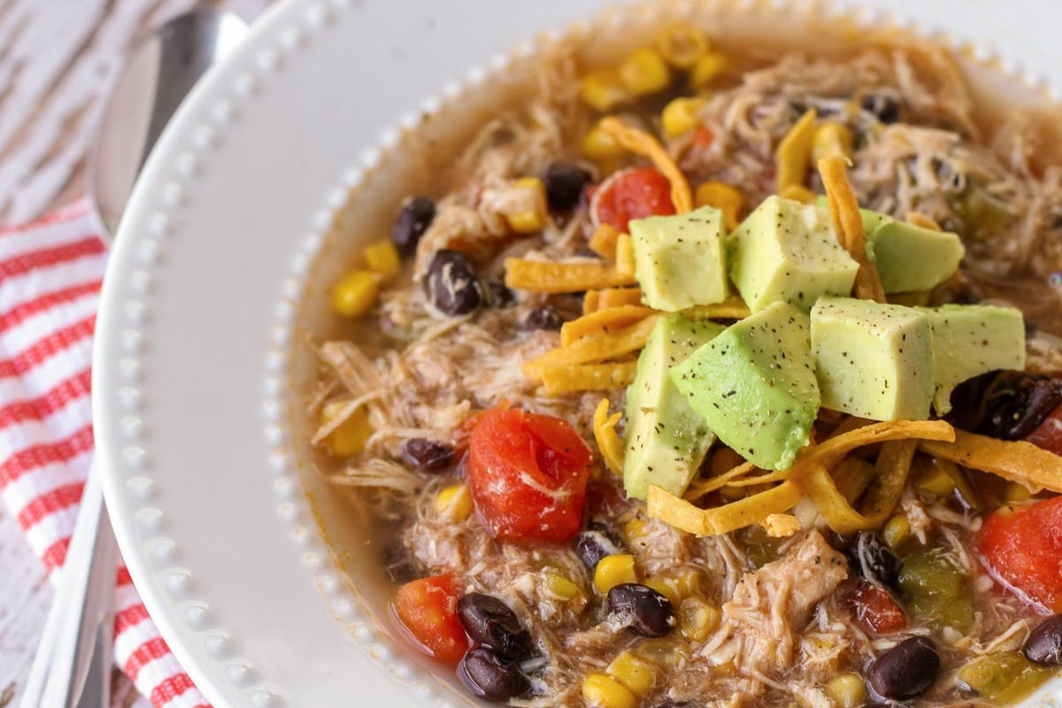 Chicken Tortilla Soup in bowl with tortilla strips and avocado