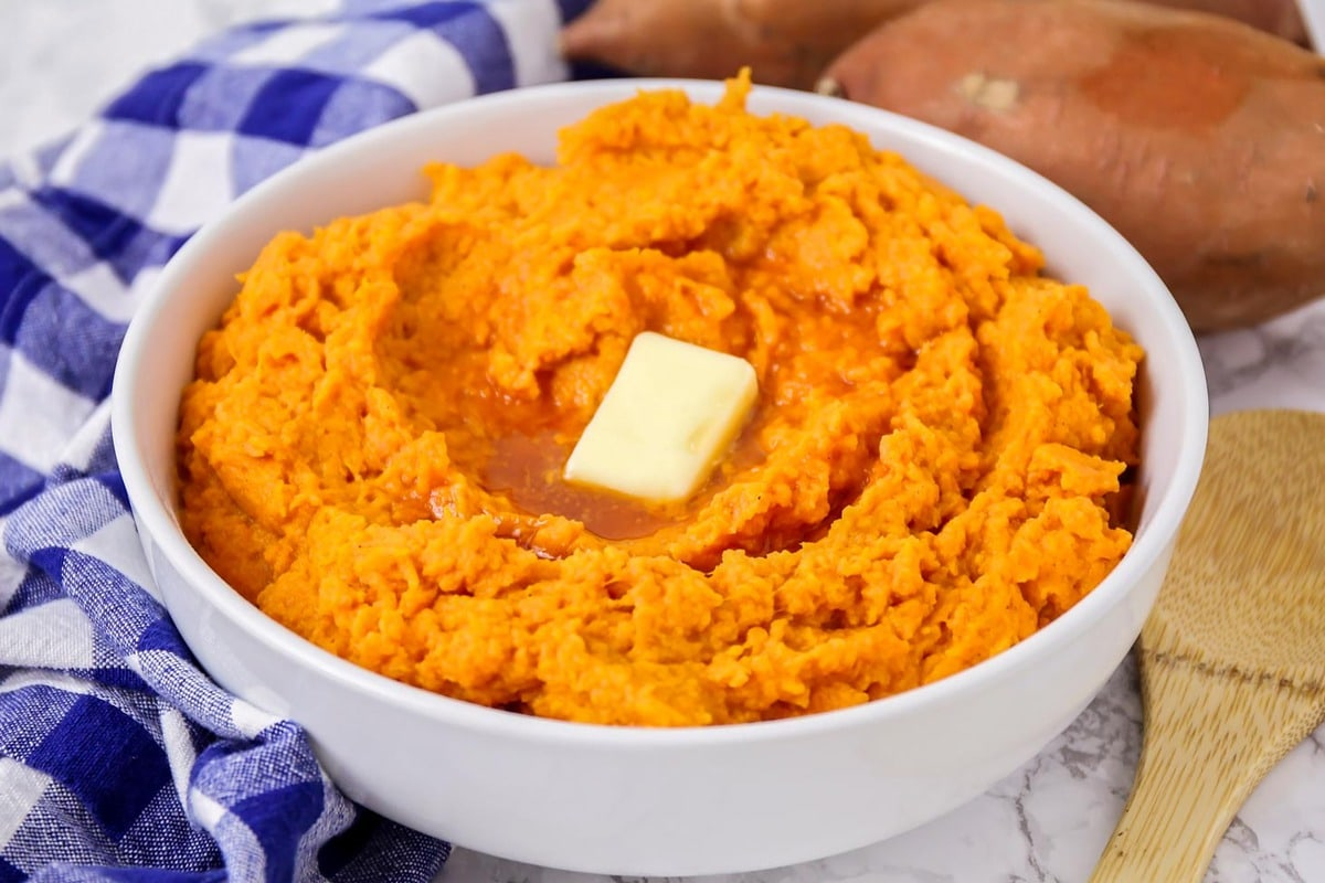 Mashed sweet potatoes in a bowl with a pat of butter on top