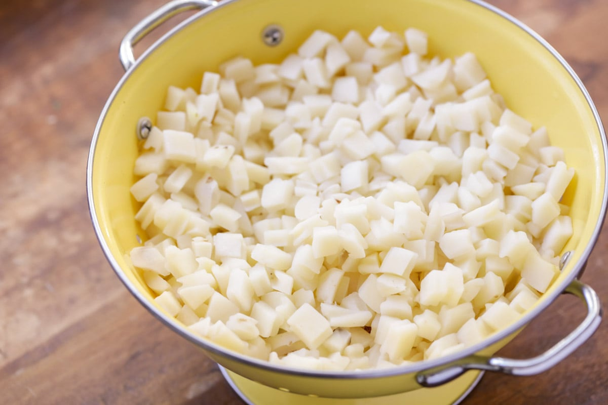 Frozen cubed potatoes thawing in collander