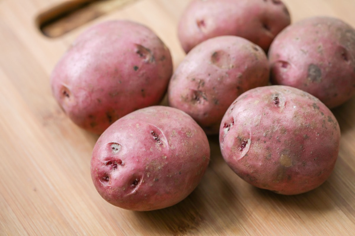 Red potatoes on cutting board for twice baked potatoes casserole